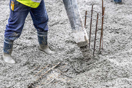 concrete form: Detail of construction site - worker pouring cement and concrete with pump tube