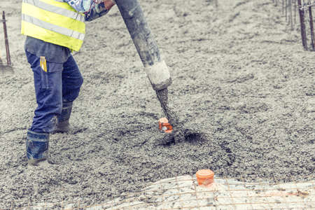 Construction worker pouring concrete, directing the pump and working in foundation Stockfoto