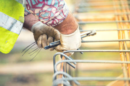 secure site: worker hands using steel wire and pincers to secure steel bars, preparing for concrete pouring on construction site Stock Photo