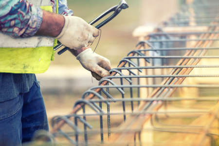 reinforcing bar: worker hands using steel wire and pliers to secure bars on construction site and preparing for concrete pouring