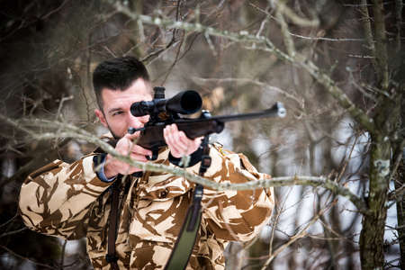 chase: Hunting, army, military concept - sniper holding rifle and aiming at target in the forest during operation