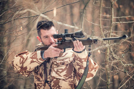 sniper training: Man holding a sniper and shooting on an open season, looking through scope Stock Photo