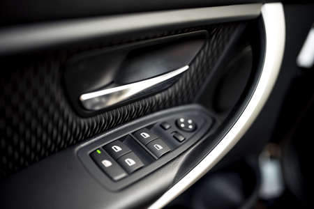 car lock: car interior details of door handle with windows controls and adjustments. Car window controls and details