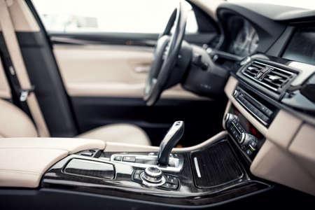 nowy: Beżowy i czarny nowoczesne wnętrze nowoczesnego samochodu, close-up szczegóły automatyczną skrzynią biegów i dźwignia zmiany biegów przeciwko tle kierownicy i desce rozdzielczej