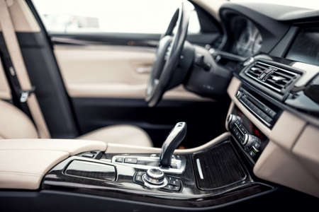 Modern beige and black interior of modern car, close-up details of automatic transmission and gear stick against steering wheel background and dashboard Stockfoto