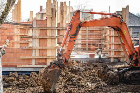 earth moving equipment: track-type excavator loader working on earth and loading at house construction site Stock Photo