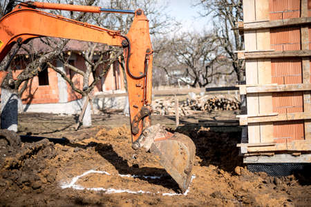 earth moving: excavator scoop on construction site, digging earth and loading dumper trucks.