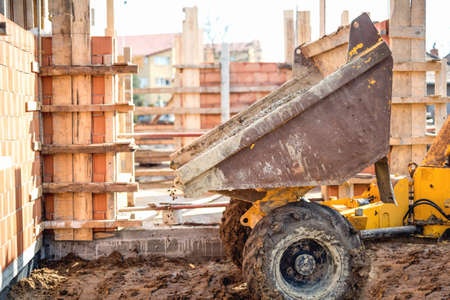 dumptruck: Dumper truck unloading gravel, sand and stones at construction site. Brick layering and working at construction site