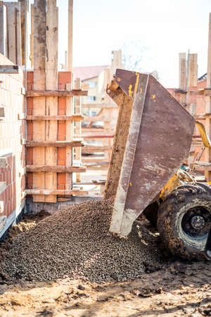 building foundation: Dumper truck unloading construction gravel, granite and crushed stones at building foundation