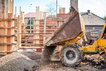 industriële truck loader uitgraven grind en bouw aggregaten. Bouwplaats met kipwagenvrachtwagen en materialen Stockfoto