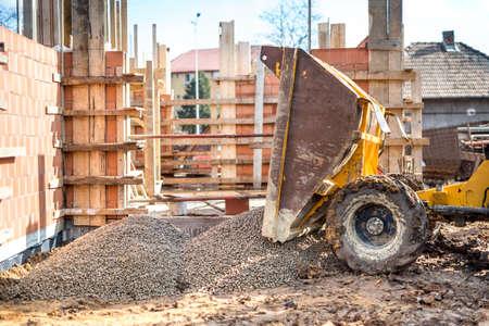 dumptruck: industrial truck unloading gravel with excavator and backhoe on construction site