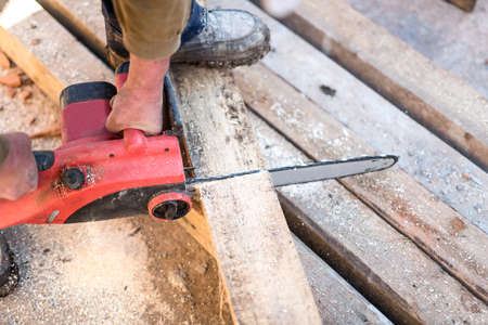 contruction: worker cutting wooden boards on contruction site with electric circular saw