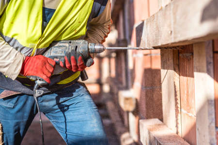 herramientas de carpinteria: Trabajador que usa una herramienta eléctrica de perforación en el sitio de la construcción y la creación de agujeros en ladrillos