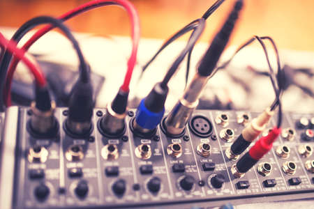 Audio and video jack cable connected at rear end of receiver, amplifier or music mixer at concert, party or festival. Soft effect on photo