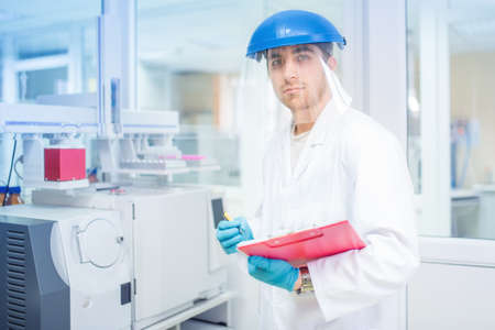 lab tech: Scientist using protective rubber gloves and helmet, doing experiments and analyzing in chemical laboratory