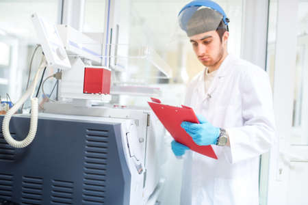 lab tech: Scientist or doctor using clipboard and reading experiment information from computer