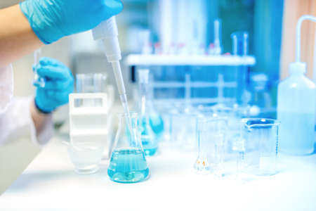 Doctor using electronic pipette for taking samples from test tube in special chemical laboratory or private clinic