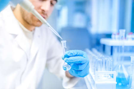 pharmaceutical research: Male scientist using medical tool for extraction of liquid from samples in special laboratory or medical room