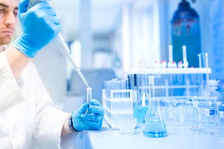 Reageerbuisjes in de kliniek, apotheek en medisch onderzoek laboratorium met mannelijke wetenschapper met een pipet Stockfoto