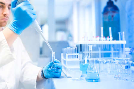 researching: Test tubes in clinic, pharmacy and medical research laboratory with male scientist using pipette Stock Photo