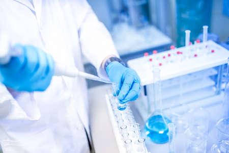 científico manos con gotero o pipeta, que examinan muestras y líquidos