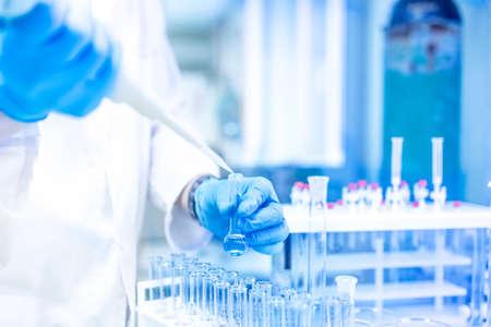 Medische Scientist en apotheek in het laboratorium met behulp van een pipet of druppelaar voor vloeibare monsters Stockfoto