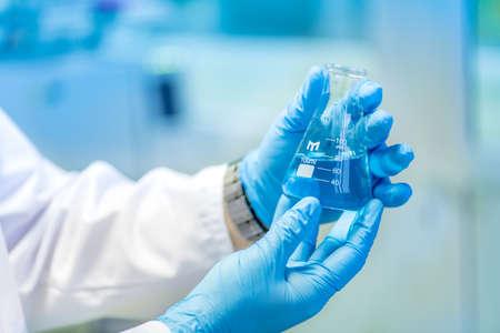 laboratorio: Doctor que sostiene un tubo de ensayo, un frasco con l�quido azul en laboratorio especial preparaci�n para experimentos y tratamientos Foto de archivo