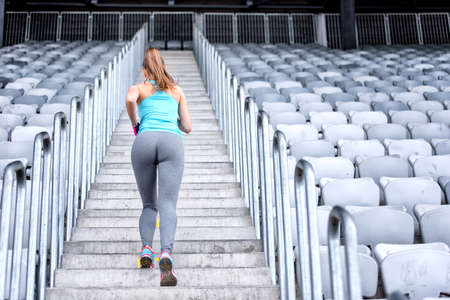 healthy fitness woman jogging and running outdoors in city stadium, working out on stairs photo