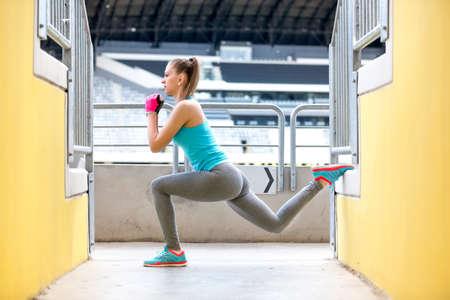 sexo femenino: Corredor femenino estiramiento y hacer sentadillas después de correr entrenamiento. Concepto de la aptitud en el estadio