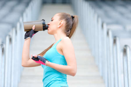 Portrait of healthy fitness girl drinking protein shake. Woman drinking sports nutrition beverage while working out