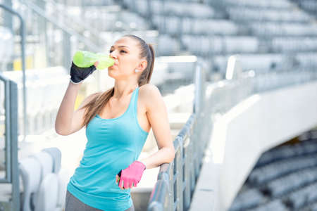 Fitness concept - young woman drinking water during workout, training. Cross fit workout on stairs, squats and exercises Фото со стока