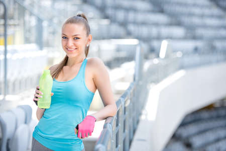 Smiling blonde fitness woman drinking water after complete outdoor workout