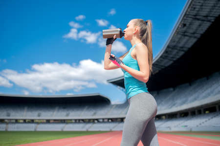 Portrait of healthy fitness girl drinking protein shake during workout on stadium Imagens