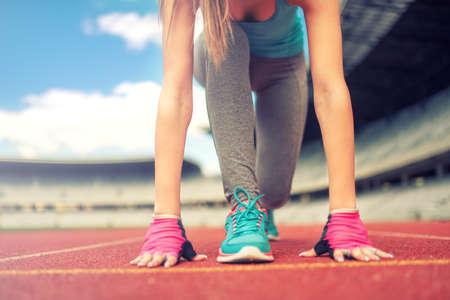 atleta corriendo: Mujer atl�tica que ir a correr o correr en la pista de atletismo. Concepto de fitness saludable con estilo de vida activo. Foto de archivo