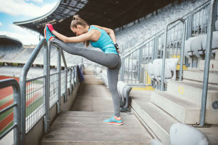 Fitness young woman stretching outdoors and doing warm up exercises. Training and working out sportswoman concept. Vintage, soft effect on photo Stock Photo