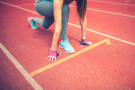 fitness motivation: athlete on starting blocks at stadium track preparing for a sprint. Fitness, healthy lifestyle concept