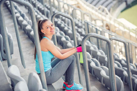 good quality: female fitness instructor resting and excercising. sportswoman enjoying a good, quality workout on stadium stairs Stock Photo