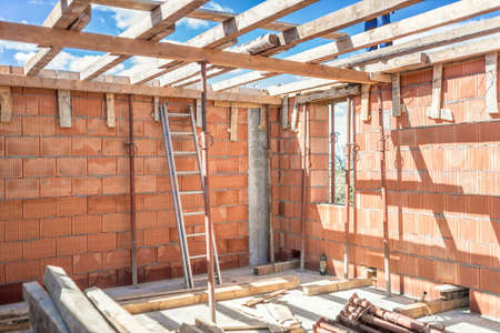 mud house: Construction site tools and details - metal ladder, brick layers, wood and timber Stock Photo