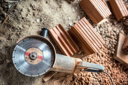 grinder: Angle grinder used on construction site for cutting bricks, debris. Tools and bricks on new building site