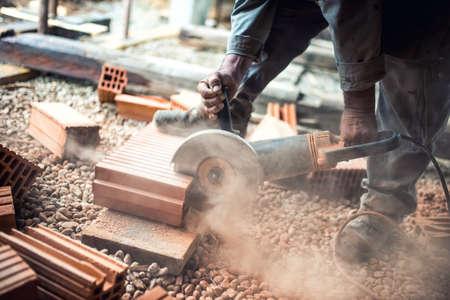 polvo: Trabajador de la construcci�n industrial utilizando una amoladora angular profesional para el corte de ladrillos y la construcci�n de paredes interiores