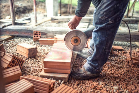 sawing: Industrial worker using an grinder for cutting and sawing construction bricks