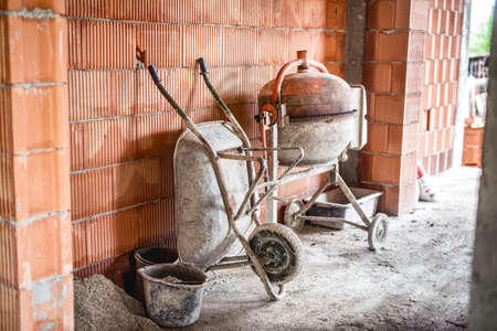 after hours: Cement mixer machine, wheel barrow and other construction site tools after working hours Stock Photo