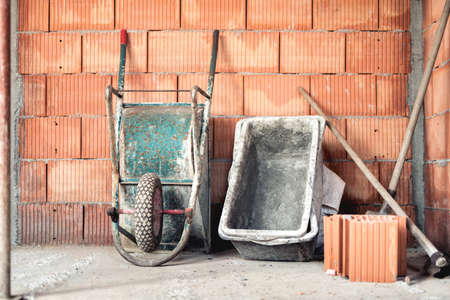 putty: Brick layering with mortar, wheel barrow and cement mixer on construction site