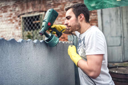 Professional construction worker painting walls at house renovation. Exterior building renovation with spray gun painter Imagens