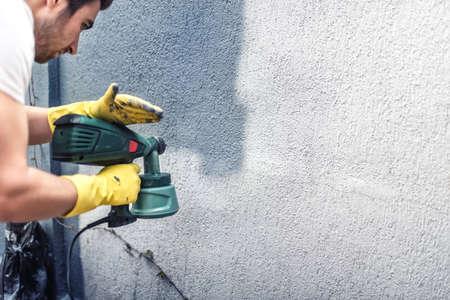 HOMBRE PINTANDO: Hombre que pinta una pared gris, la renovación de las paredes exteriores de la nueva casa
