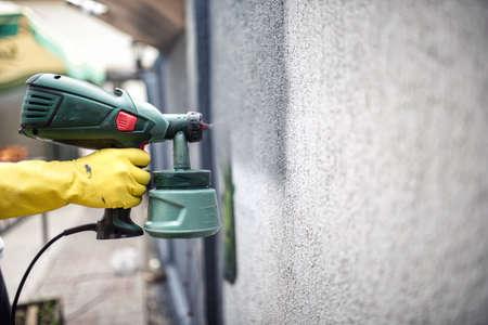 hombre pintando: Pared de la pintura del trabajador con pintura gris con pistola profesional. Pared de la pintura del hombre usando guantes de protecci�n