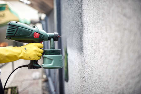 Worker painting wall with grey paint using a professional spray gun. Man painting wall using protective gloves