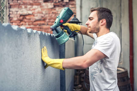peintre en b�timent: Homme utilisant des gants de protection peinture un mur gris avec de la peinture au pistolet. Jeune travailleur maison r�novation Banque d'images