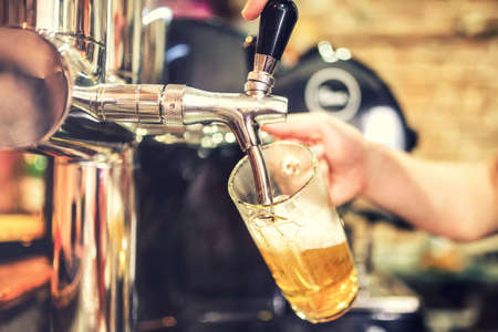 glasses of beer: barman hand at beer tap pouring a draught lager beer serving in a restaurant or pub Stock Photo