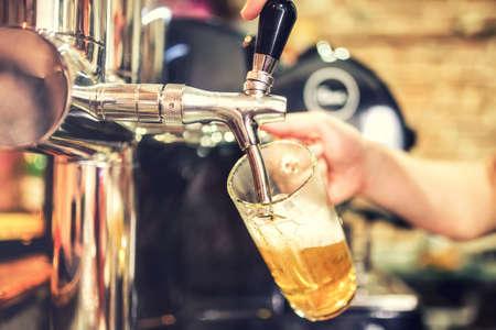 cerveza: mano barman en grifo de cerveza que vierte una cerveza lager de barril que sirve en un restaurante o pub